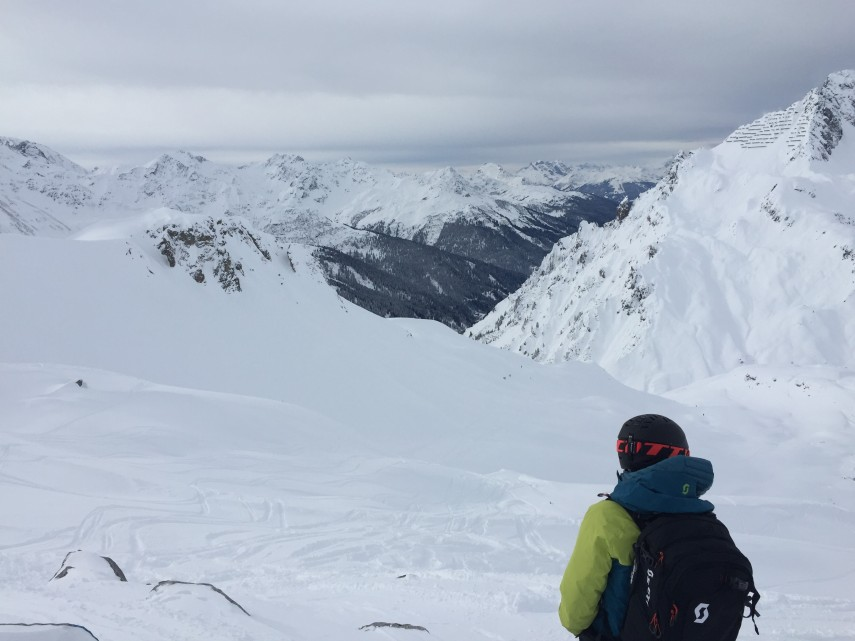 skier looking down over snowy mountain